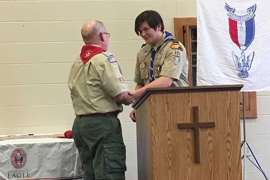 Junior Marshall Perryman giving his grandfather, Clifton Ottaway, a mentor pin. He was to give the mentor pin to someone who has helped him through his journey in becoming an Eagle Scout.