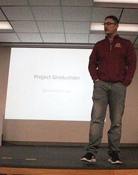 Math instructor Jerett Pfannenstiel explains Project Graduation to the senior class.