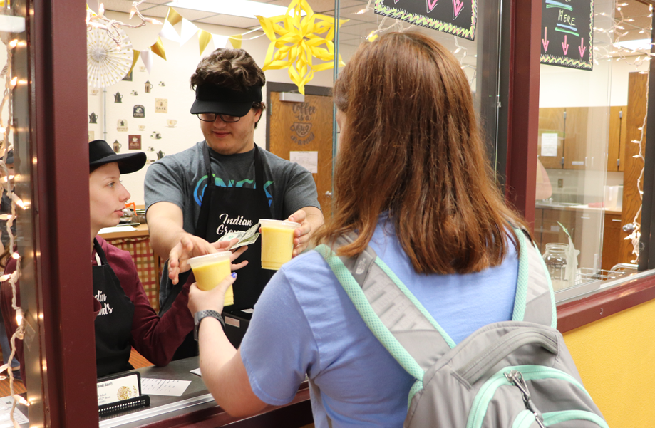 Junior Delaney Maier purchases a smoothie from the Helping Hands café, Indian Grounds.