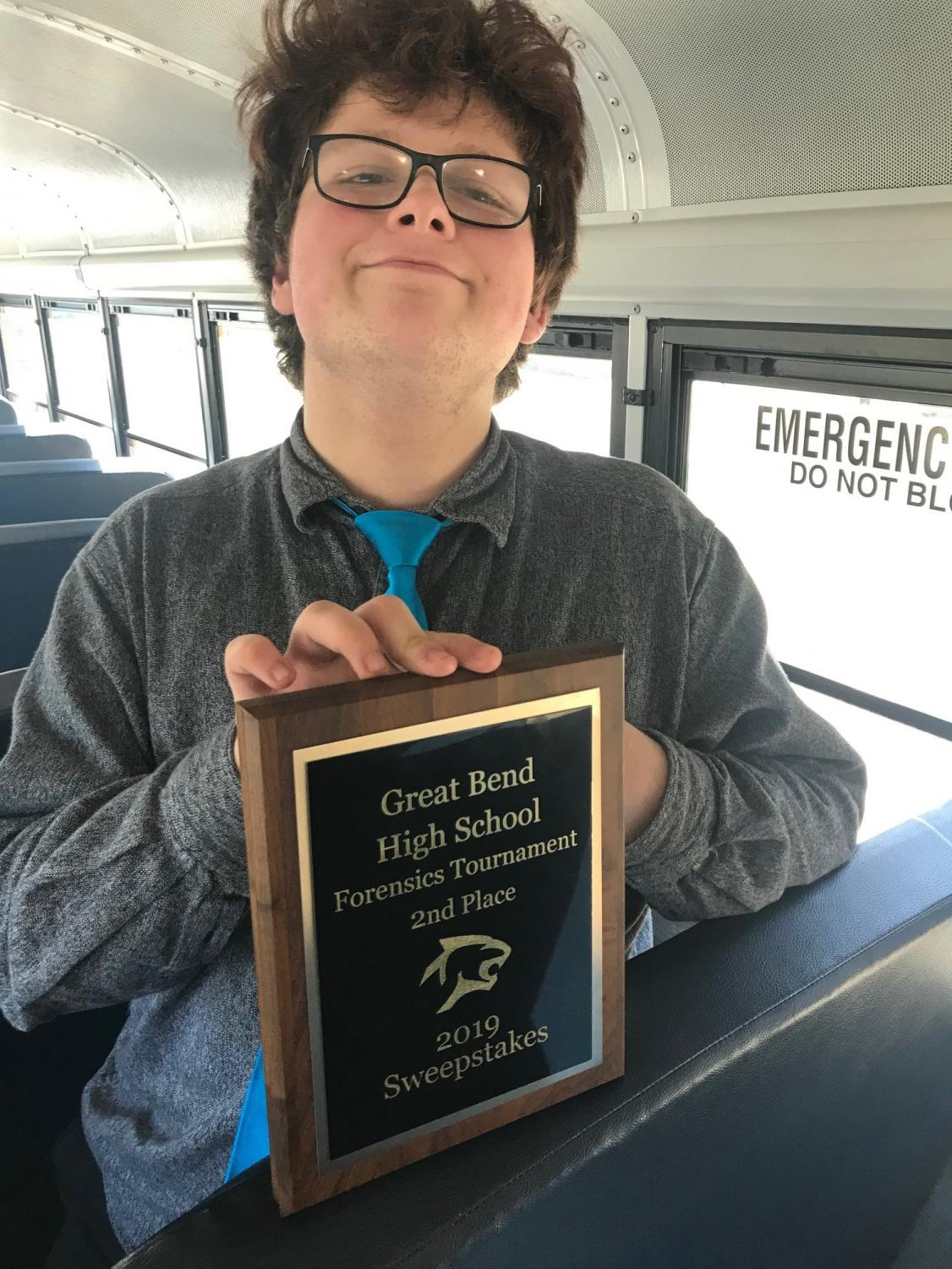Senior Neil Raynesford poses with the second place plaque from the forensics tournament at Great Bend on March 30.