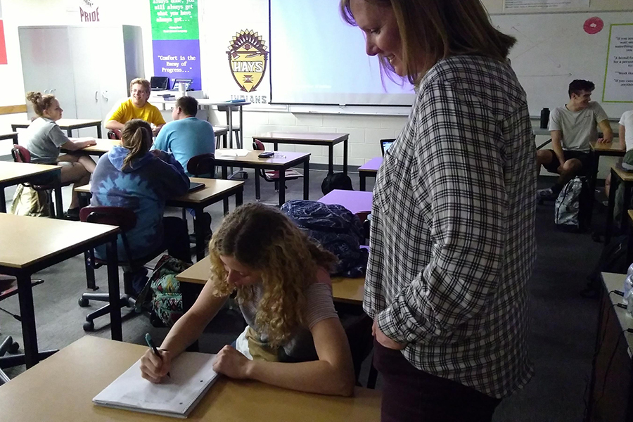 Substitute teacher Kim Fletcher helps sophomore Madison Davis understand an assignment. Fletcher substituted for business instructor Silas Hibbs' Business Economics class.