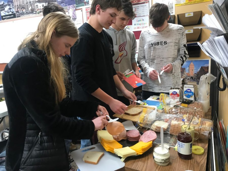 Students gather around the table to try a German continental breakfast on April 12.  The breakfast consisted of bread, sliced meat, cheese, butter, mustard and jam.