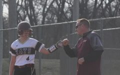 Junior Madelyn Waddell on first being congratulated by coach on first.