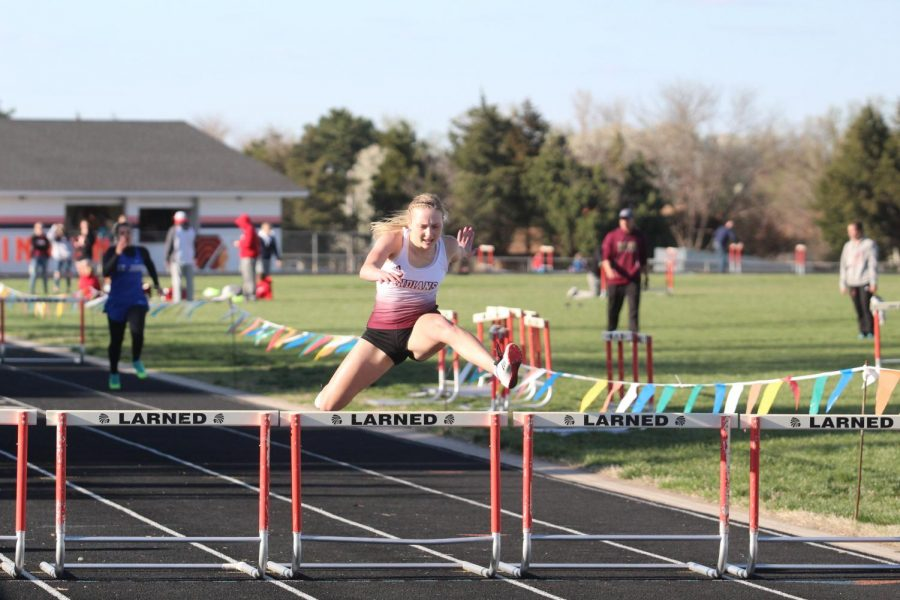 Sophomore Brooklyn Schaffer competes in hurdles at a previous meet at Larned. Schaffer and seven other athletes qualified for the 5A State Track and Field Championship.