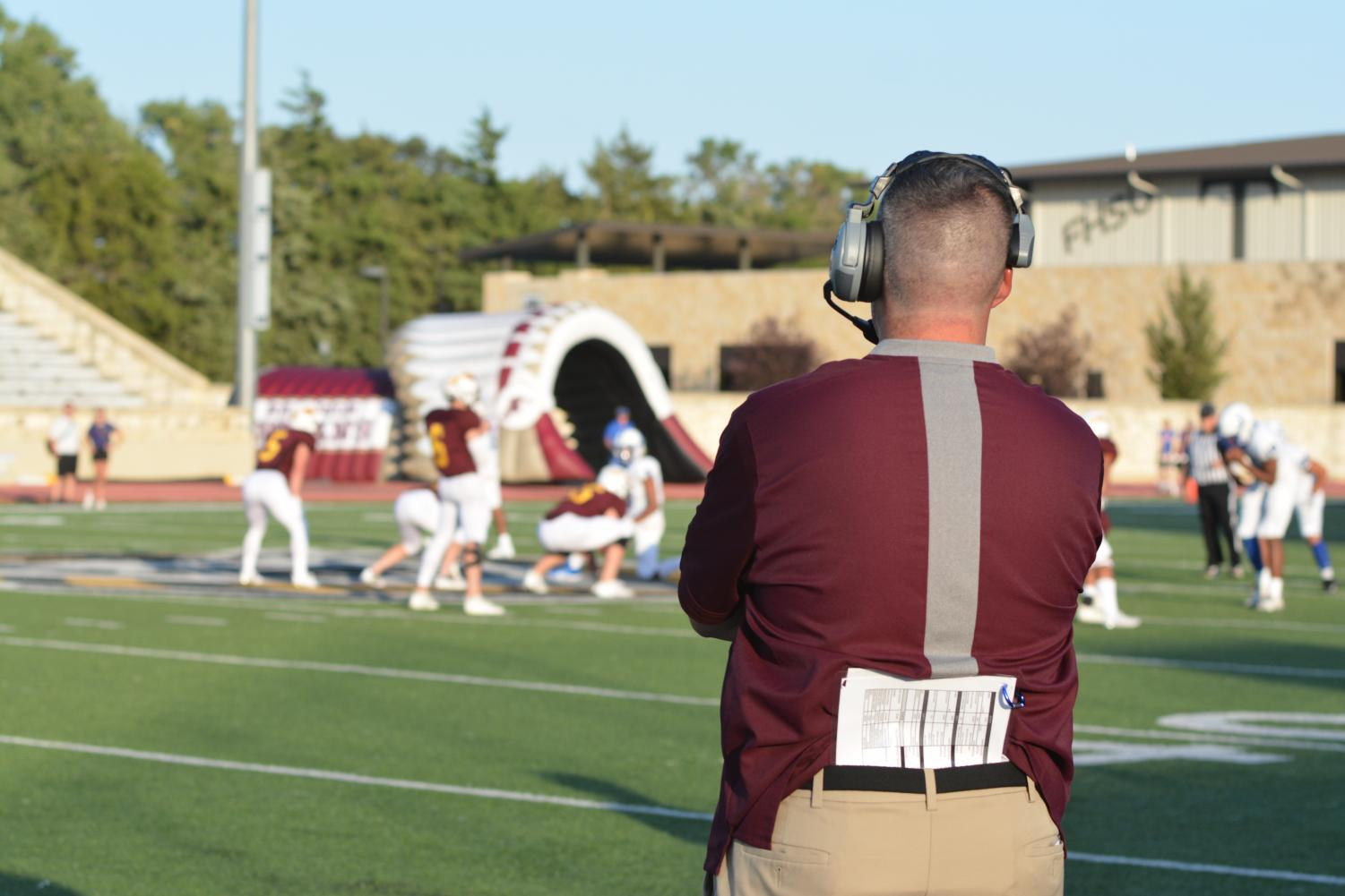 Coach Tony Crough watches from the sideline as the Indians run an offensive play.