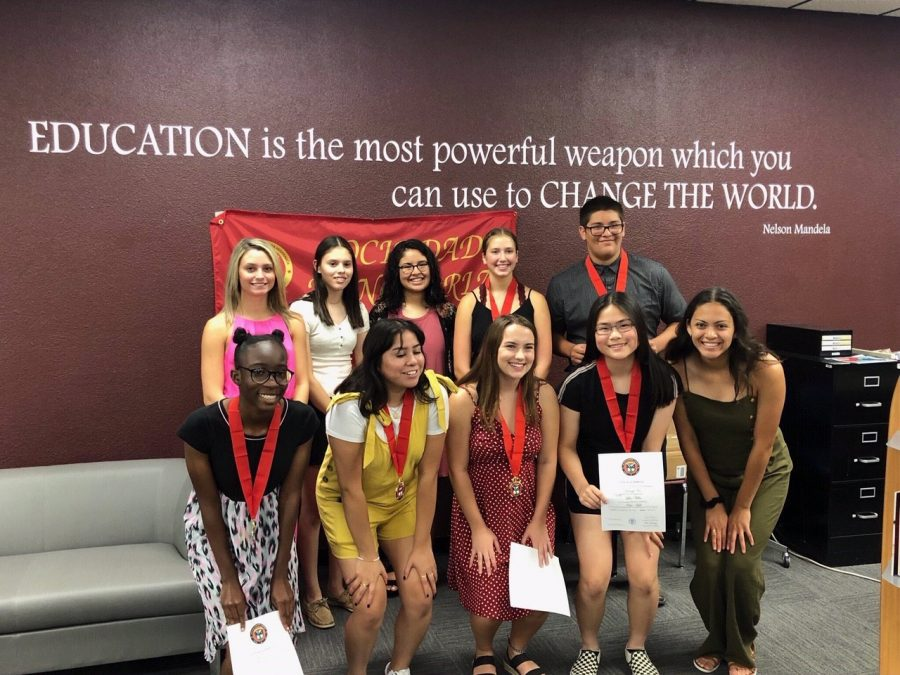 Students+inducted+into+the+Foreign+Language+Honors+Society+pose+for+a+picture+with+returning+members+after+the+ceremony.+Induction+took+place+on+Sept.+10+in+the+library.