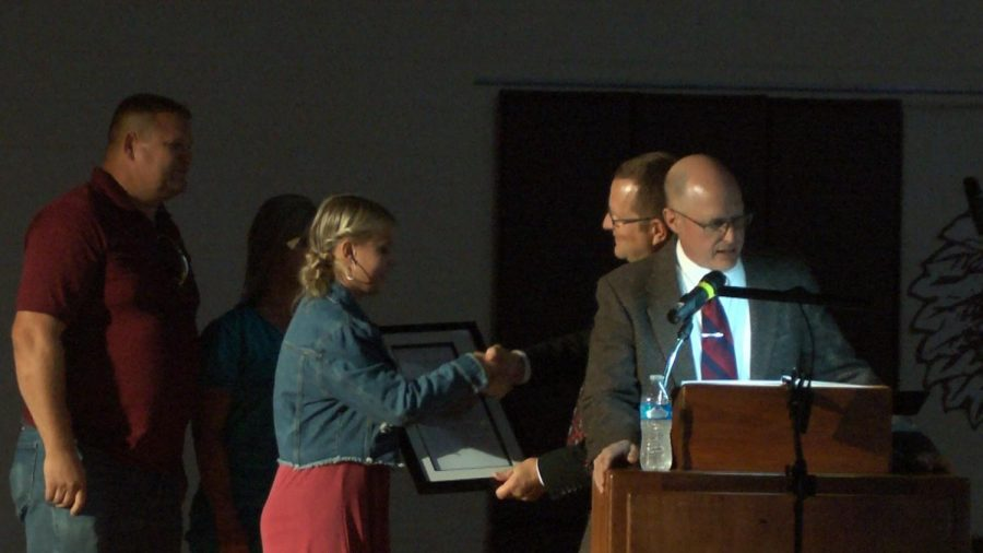 Senior Taylor Weidenhaft shakes principal Martin Straub's hand during the homecoming formal assembly. Weidenhaft was recognized for being a Nation Merit Commended student for her work on the 2019 PSAT/NMSQT.