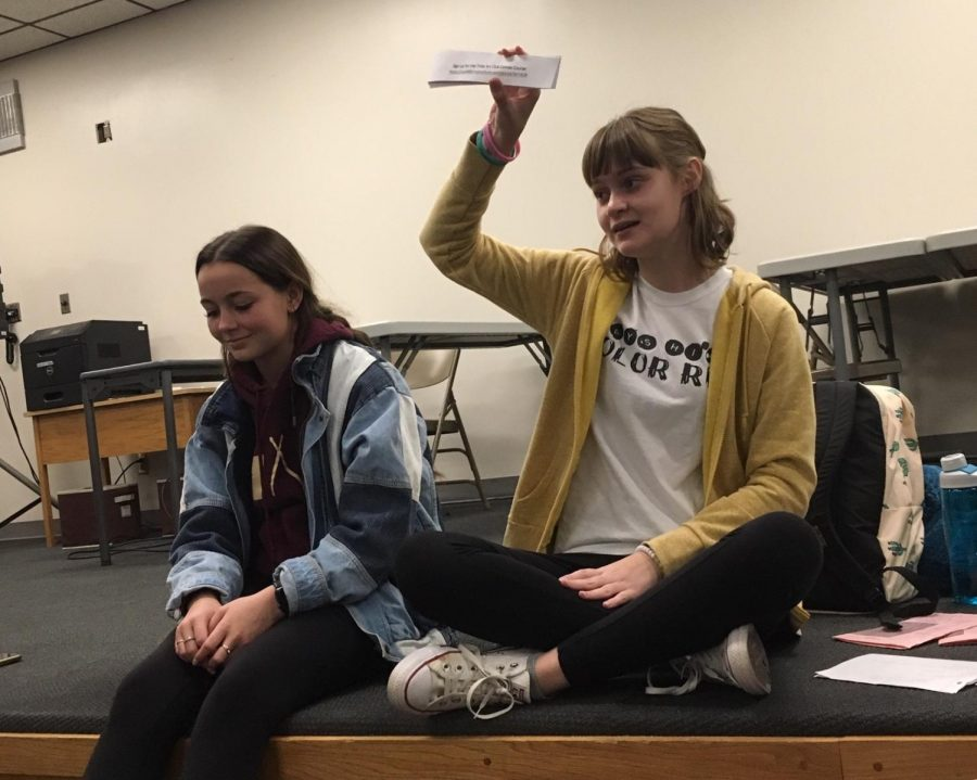 Tribe Art Club President Olivia Reed (right) holds up pieces of paper with the link to the Tribe Art Club Canvas Course. Reed gave each member a slip of paper so they could access the page.