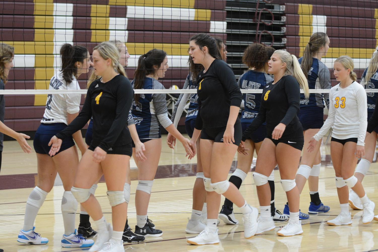 Seniors Macee Altman and Peyton Niernberger give the opposing team high fives after playing them at home on Aug. 31.