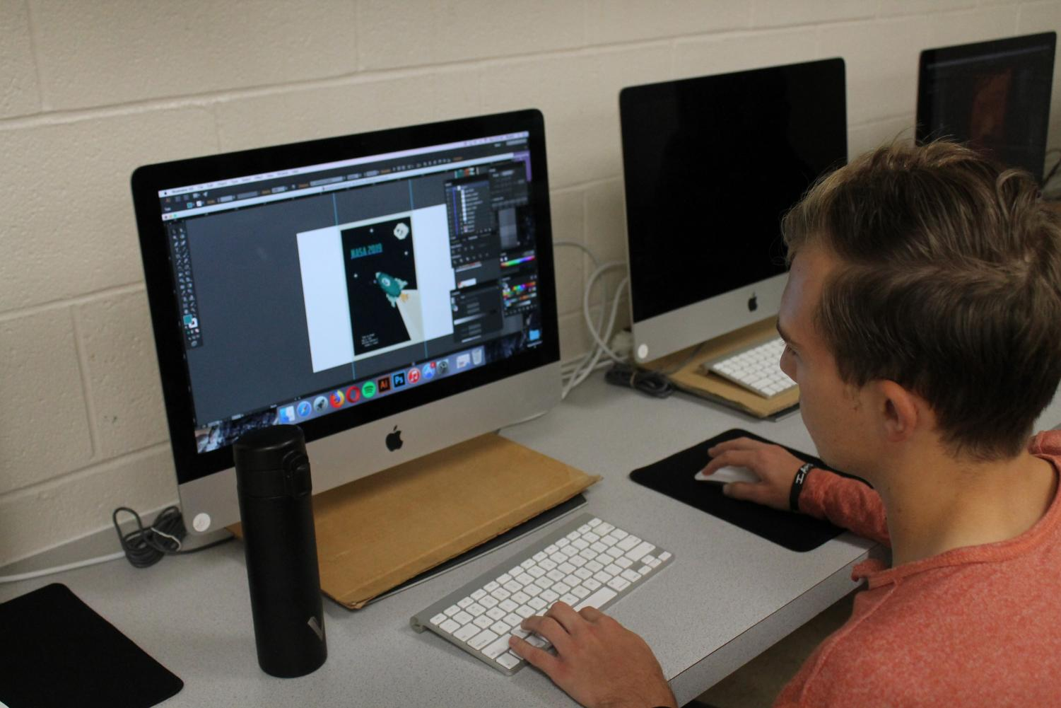 Senior Nathan Erbert works on his design for Wichita State University's NASA 60th anniversary poster competition.