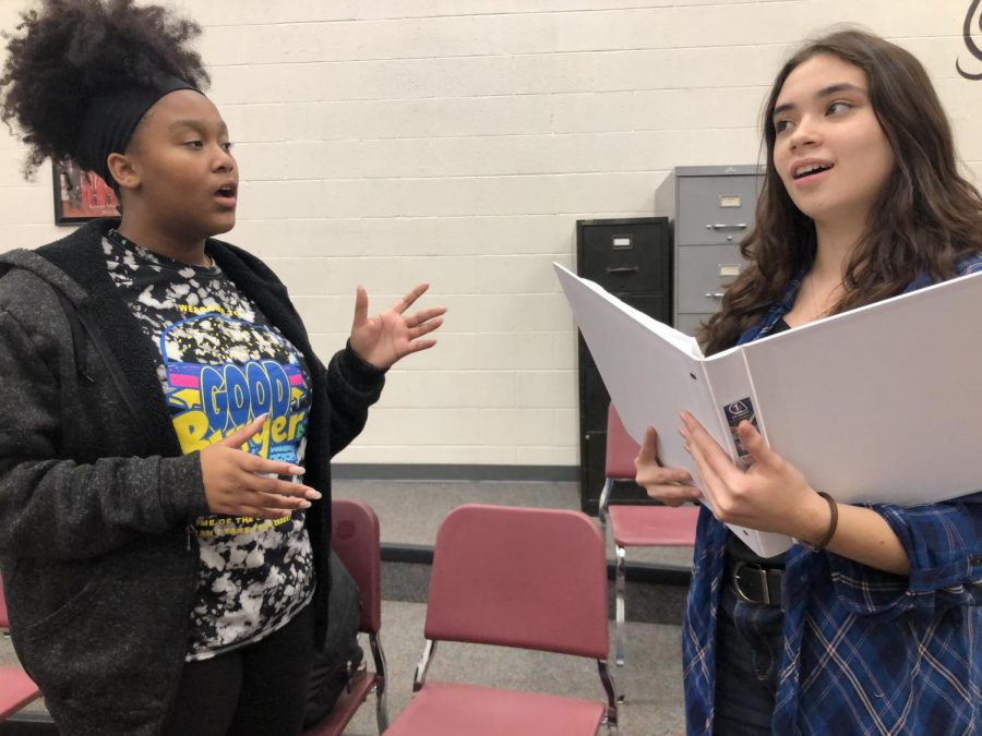 Junior Alisara Arial helps sophomore Shirley Lee run through the lyrics to her song before the showcase at the Hays Optimist Club meeting at Whiskey Creek. The performances for this year's musical,