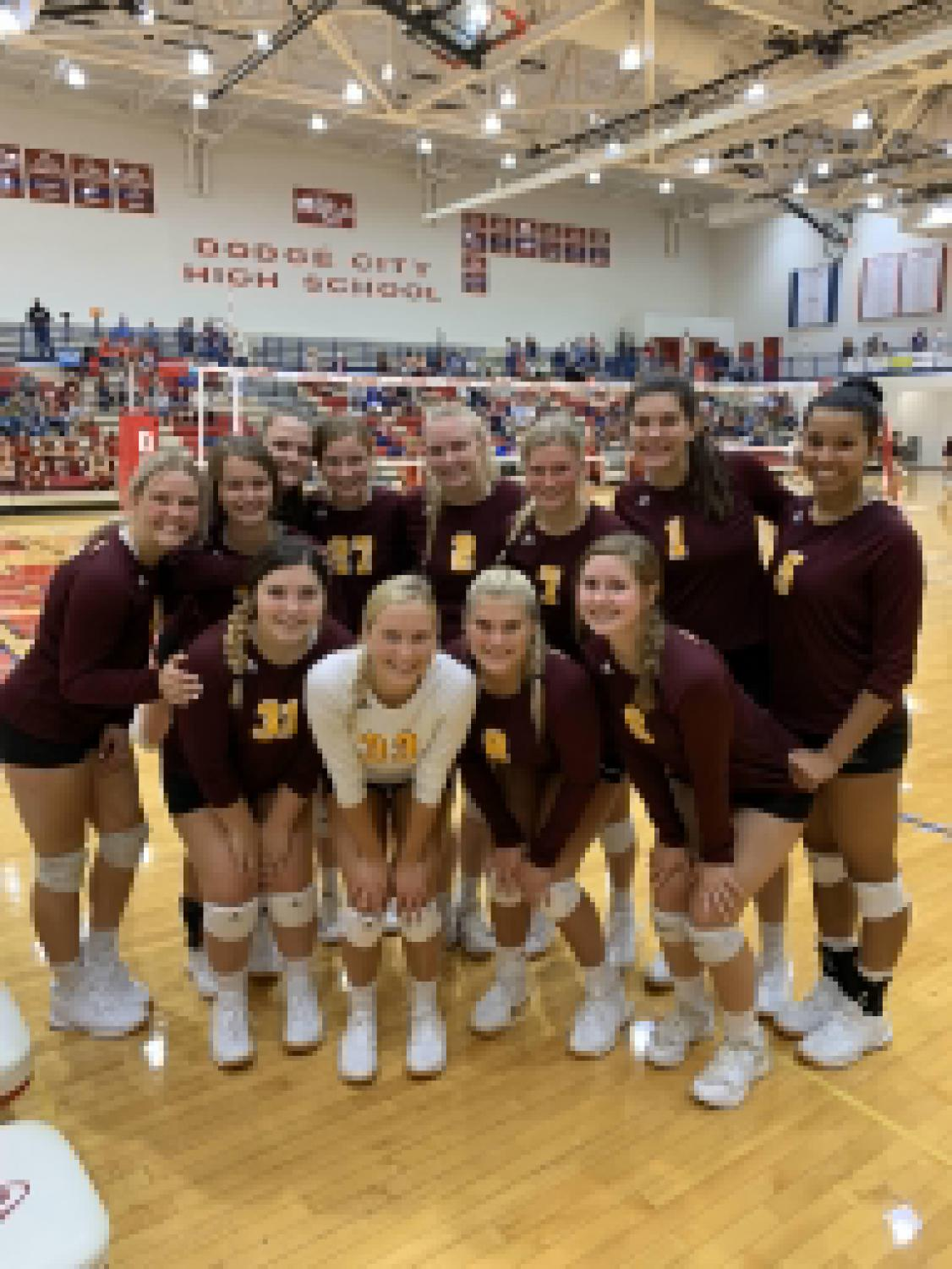 The varsity volleyball team smiling for a picture in between games at Dodge City.