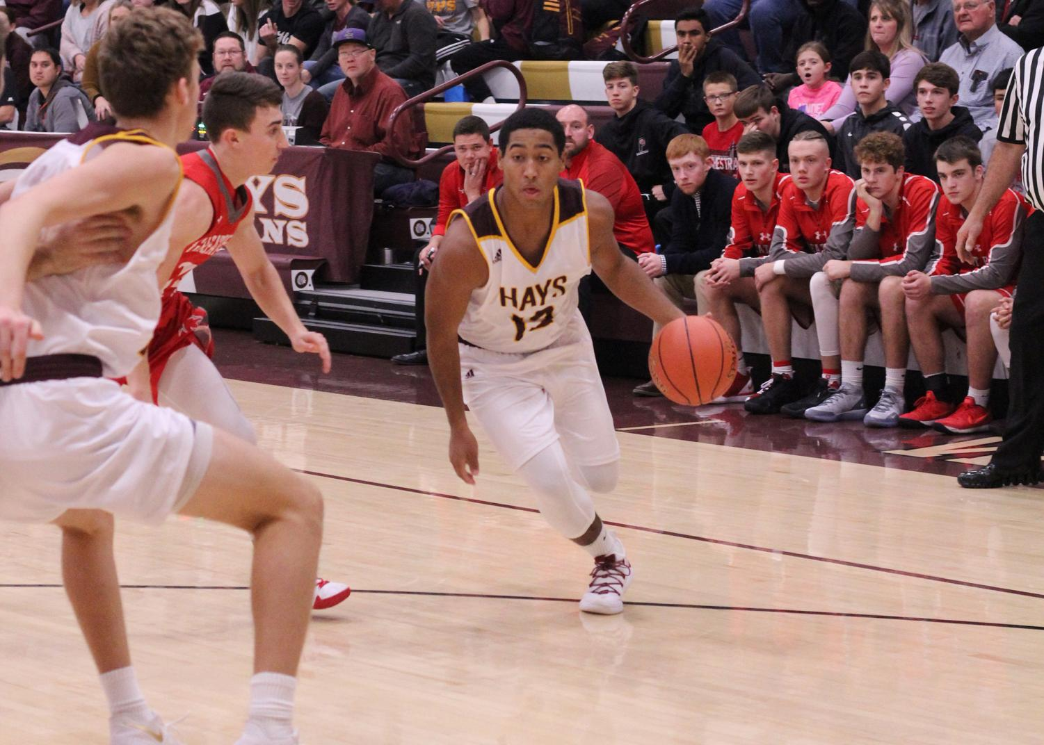 Tradgon McCrae a 2019 graduate dribbles the ball down the court during a basketball game at home last year.