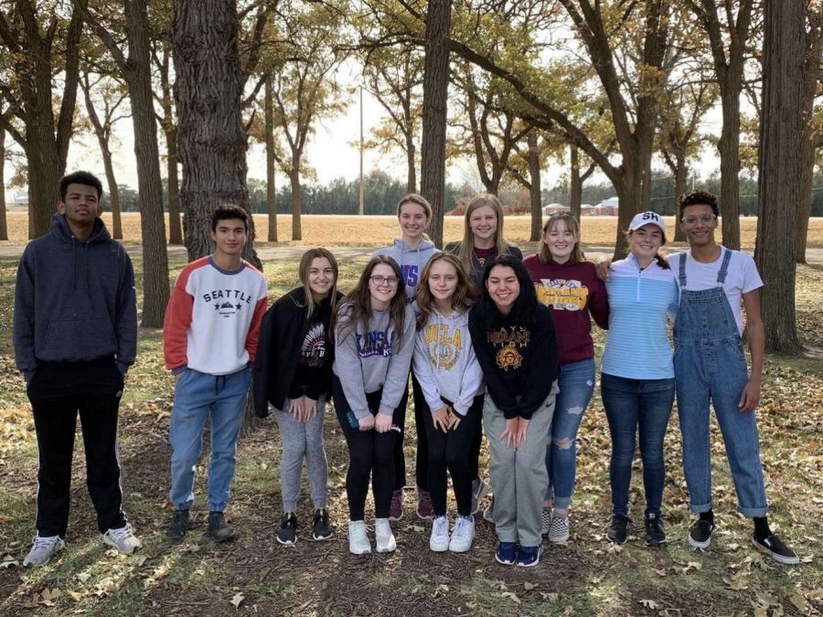 The students that attended the scavenger hunt posed for a group photo after having snacks and playing in the leaves.