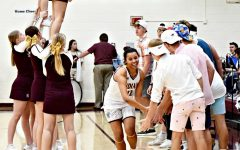 Senior Tasiah Nunney runs past the student section offering her high fives before the game on Feb. 28.