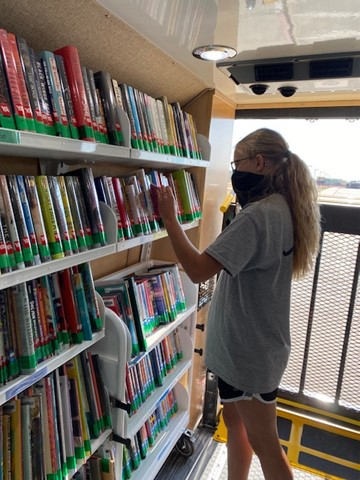 Sophomore Michaela Dickman sorting through the large display of books inside the Bookmobile.