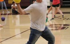 Junior Kyle Mortensen throws the yellow dodgeball during the team building activity.