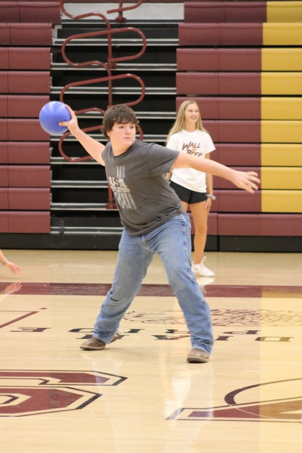 Junior Gage May throws a dodgeball during the team building activity.