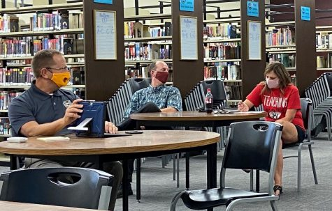 From left to right, principal Martin Straub, Joe Lohmeyer and Misty Lohmeyer sit in the library during the Site Council meeting. Misty Lohmeyer was instated as the Site Council president during the meeting.
