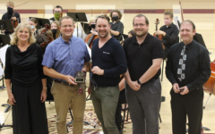 Orchestra director Joan Crull, principal Martin Straub, vocal director Alex Underwood, band director Matthew Rome and assistant orchestra director Nathan Mark pose in front of the Concert Orchestra after awarding Straub with his KMEA Honor Administrator of the Year plaque at the Fall Orchestra Concert that was held on Oct. 13 in Gym A.