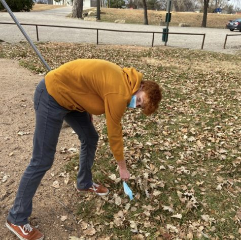 """Senior Skylar Zimmerman picks up a dirty mask. This was to complete the """"Cleanup Crew"""" task where a member of the team needed to properly dispose of litter found during the hunt."""