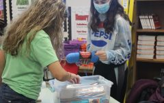 Sophomore Rylie Fairbank and junior Rachel Windholz pick out their knitting needles to start their projects.