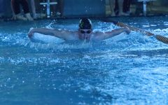 Junior Tyler Solida competes in a race using the butterfly stroke during the HHS home meet at the Center for Health Improvement