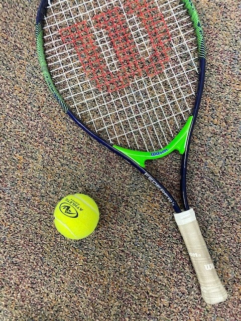 A tennis racket sitting next to a tennis ball.