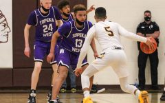 Senior Tj Nunnery dribbles the ball near a Topeka West deffender on March 9th.