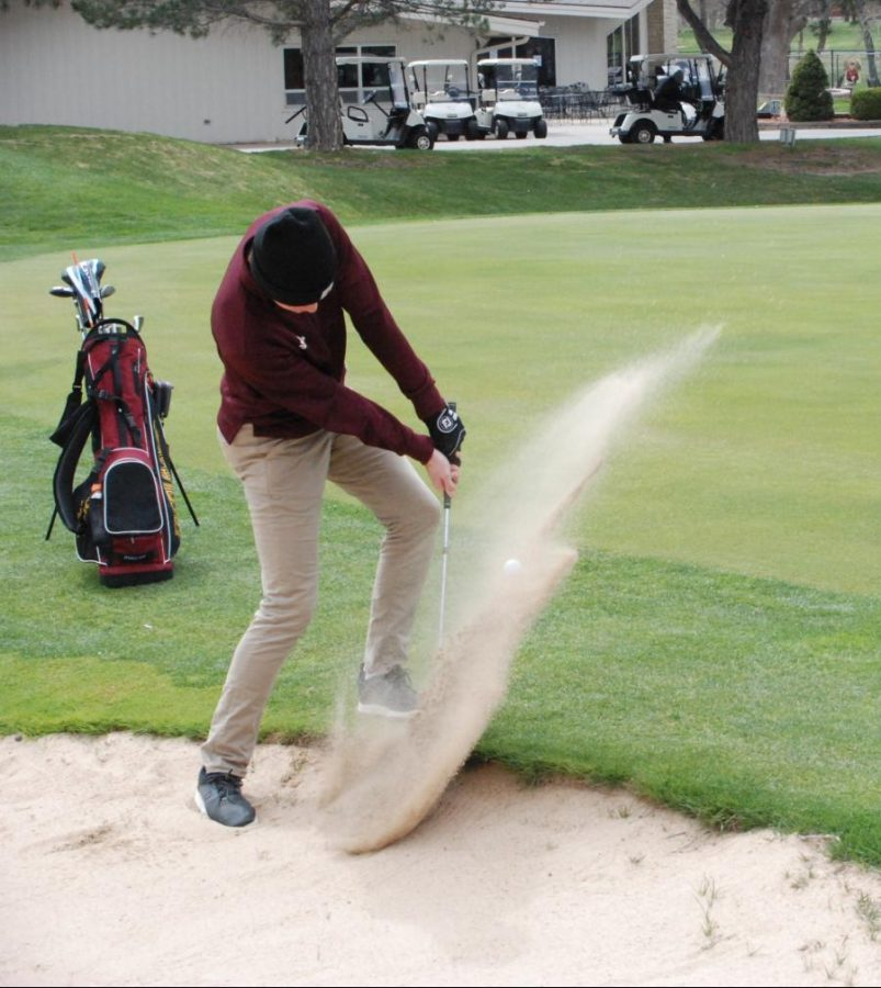 Senior Skylar Zimmerman hits out of the bunker on Hole nine at the Smoky Hill Country Club at the Hays tournament on April 19.