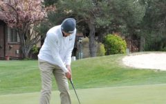 Sophomore Braden Hoskin takes a practice putt on the green of hole number nine at Smoky Hill Golf Course.