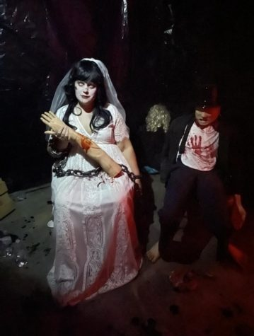 An actor in the haunted house sits in wait for customers to turn the corner into her room.